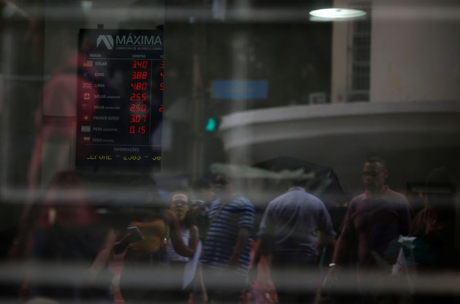 People are reflected on the glass as a board showing the Real-U.S. dollar and several foreign currencies exchange rates is seen in Rio de Janeiro
