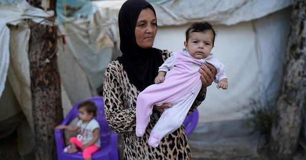 A Syrian refugee mother poses with her baby in front of their tent in Yayladagi refugee camp in Hatay province, near the Turkish-Syrian border, Turkey, Oct. 15, 2016.