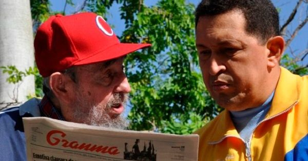 Former Cuban leader Fidel Castro and Venezuela's Hugo Chavez read a copy of the Cuban Communist Party newspaper