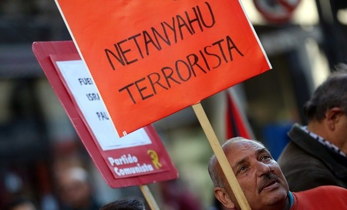 A man holds a sign that reads 'Netanyahu terrorist'